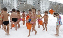 Children pour cold water on themselves during daily exercises at a kindergarten, in air temperatures of minus 25 degrees Celsius (minus 13 degrees Farenheit) in Barnaul, the capital of the Altai region, December 26, 2012. REUTERS/Andrei Kasprishin (RUSSIA - Tags: ENVIRONMENT EDUCATION)